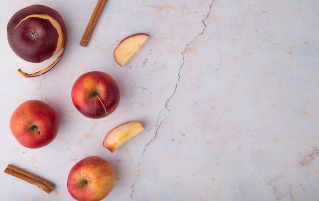 Vista superior maçãs vermelhas com canela à esquerda, com espaço de cópia no fundo branco