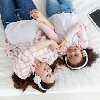 Vista superior mãe e filha ouvindo música