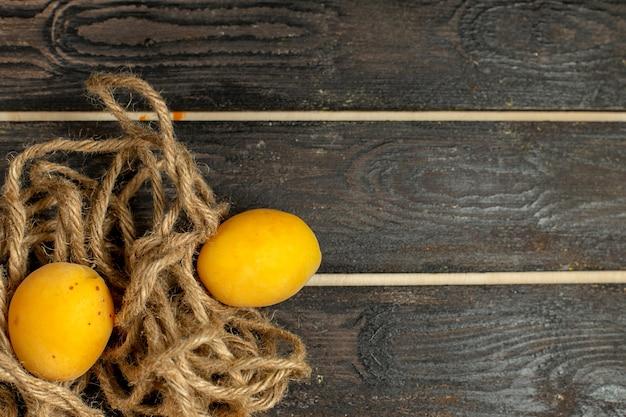 Vista superior mais de perto damascos amarelos maduros e frutas frescas no fundo marrom rústico