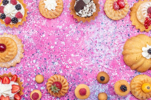 Vista superior mais de perto de bolos saborosos assados com creme junto com diferentes frutas na luz