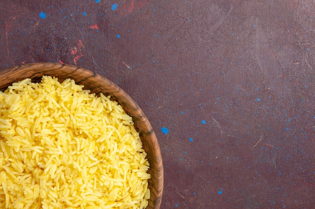 Vista superior mais de perto delicioso arroz cozido dentro de um prato marrom na mesa escura