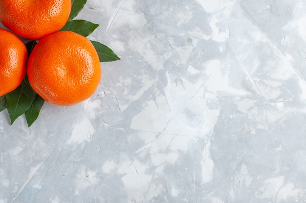 Vista superior mais de perto laranja tangerinas cítricas inteiras na mesa de luz
