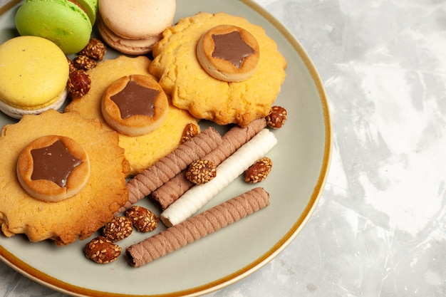 Vista superior mais de perto macarons franceses com bolos e biscoitos em uma superfície branca clara