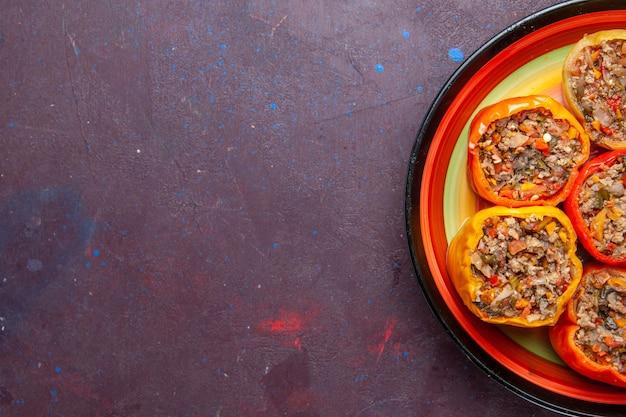 Vista superior mais de perto pimentões cozidos com carne moída em fundo cinza escuro