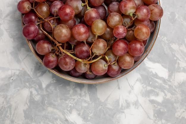 Vista superior mais de perto uvas vermelhas frescas suculentas frutas suaves e doces em uma mesa branca clara