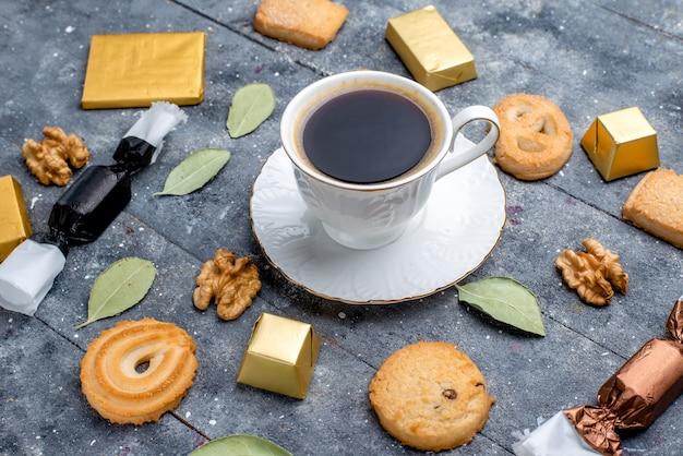 Vista superior mais próxima de uma xícara de café com biscoitos e nozes em cinza