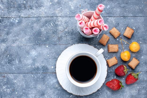 Vista superior mais próxima de uma xícara de café com morangos, biscoitos, doces de palito rosa na mesa brilhante