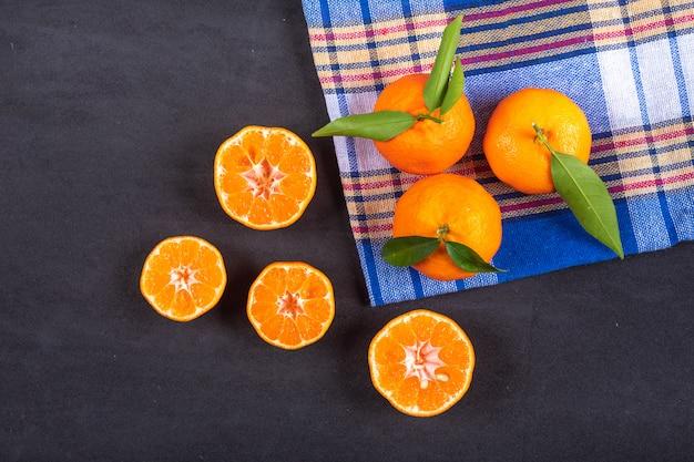 Vista superior mandarinas na toalha na superfície preta