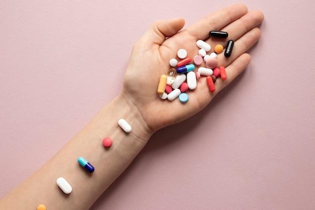Vista superior mão cheia de pílulas coloridas