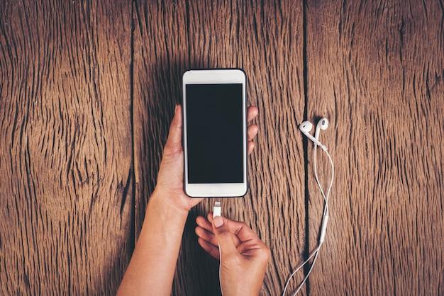 Vista superior mão cobrando telefone em fundo de madeira