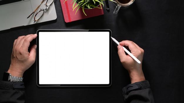 Vista superior, mão de homem segurando tablet de desenho e lápis, tablet de tela em branco de maquete