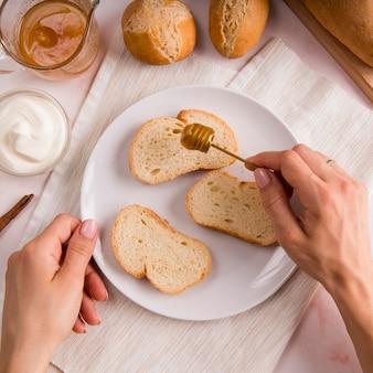 Vista superior mão derramando mel sobre fatias de pão