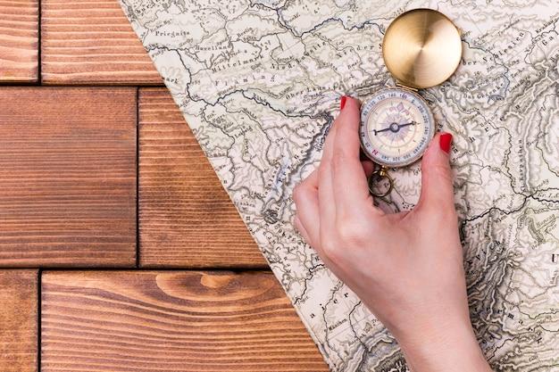 Vista superior mão segurando a bússola no topo do mapa do mundo