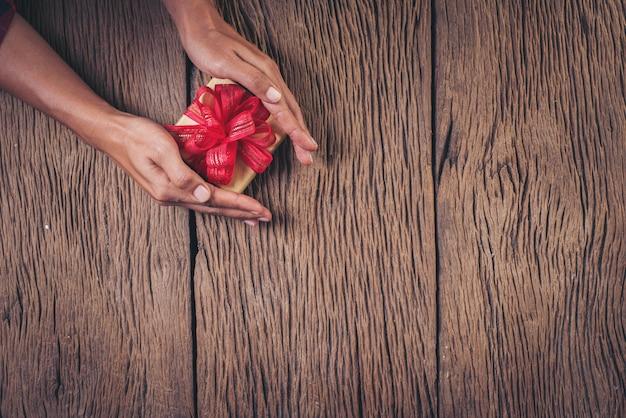 Vista superior mão segurando a caixa de presente em fundo de madeira