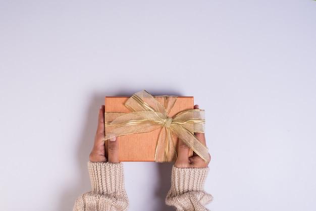 Vista superior mão segurando a caixa de presente no espaço de trabalho