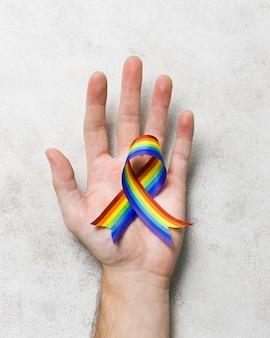Vista superior mão segurando a fita nas cores do arco-íris