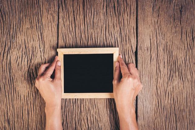 Vista superior, mão, segurando, chalkboard, ligado, madeira, fundo