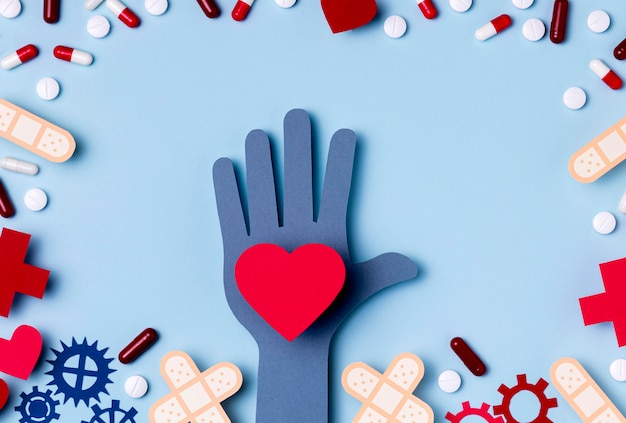 Vista superior mão segurando o coração rodeado de comprimidos