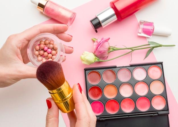Vista superior mão segurando produtos de beleza