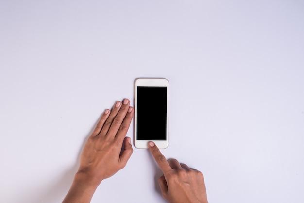 Vista superior, mão, segurando, telefone pilha, branco, fundo