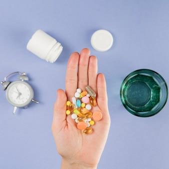 Vista superior mão segurando variedade de medicamento