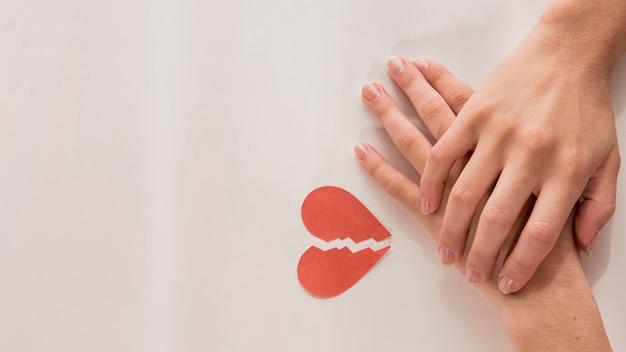 Vista superior mãos com coração partido