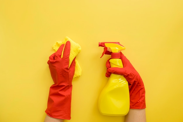 Vista superior mãos com luvas de borracha, segurando o material de limpeza