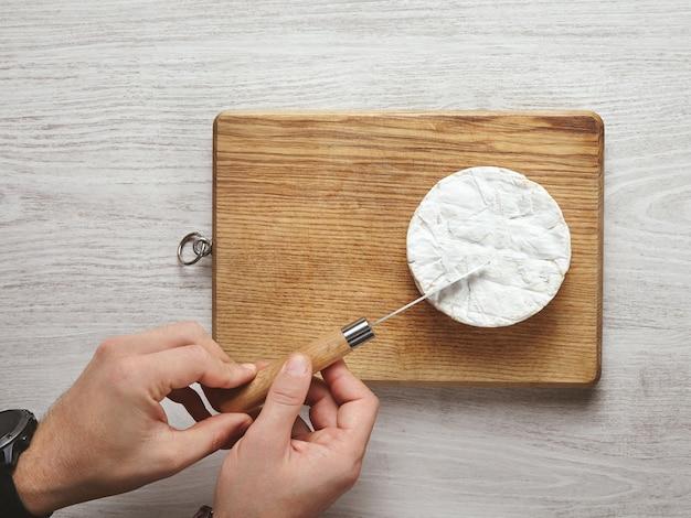 Vista superior, mãos de homem bonito e brutal cortam com precisão um pedaço triangular de queijo camembert com