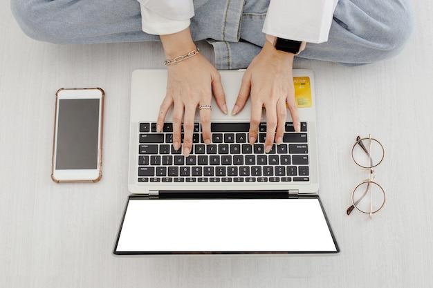 Vista superior, mãos femininas, trabalhando no laptop com óculos e smartphone.