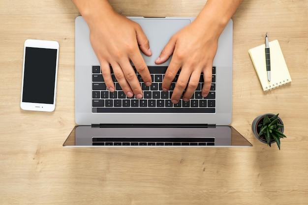 Vista superior mãos humanas trabalhando no laptop moderno, navegar on-line, digitar um texto, navegar na internet
