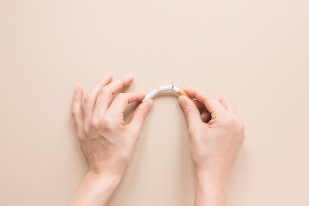 Vista superior mãos quebrando um cigarro