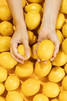 Vista superior mãos segurando limão orgânico