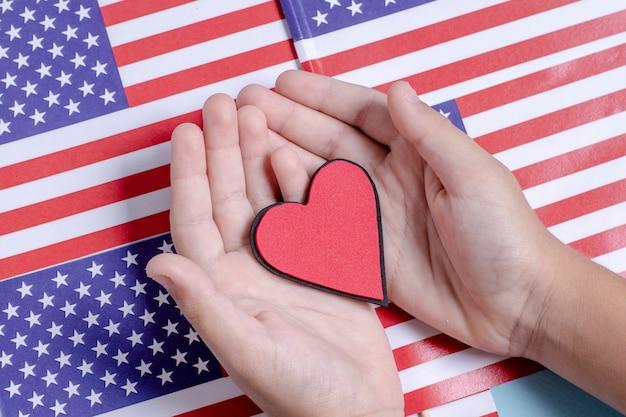 Vista superior mãos segurando um coração nas bandeiras dos eua