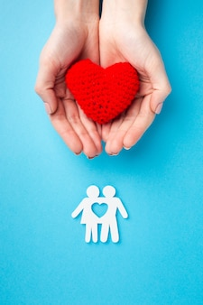 Vista superior mãos segurando uma figura de coração e família