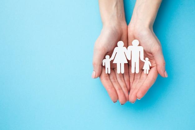 Vista superior mãos segurando uma figura de família com espaço de cópia