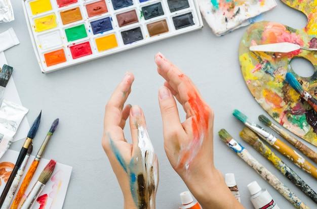 Vista superior mãos sujas com materiais de pintura