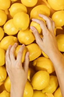 Vista superior mãos tocando limões frescos