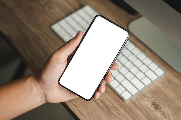 Vista superior maquete de imagem mão usando um homem smartphone segurando o telefone celular com tela em branco