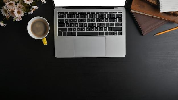 Vista superior maquete laptop, caderno, lápis e café com flores na mesa preta.