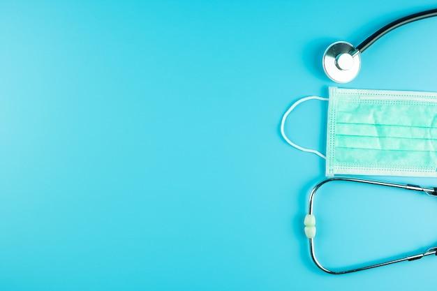 Vista superior máscara protetora e estetoscópio sobre fundo azul, com espaço de cópia de texto. proteção de coronavírus e gripe. anti-séptico, dia mundial da saúde e conceito de dia feliz médico