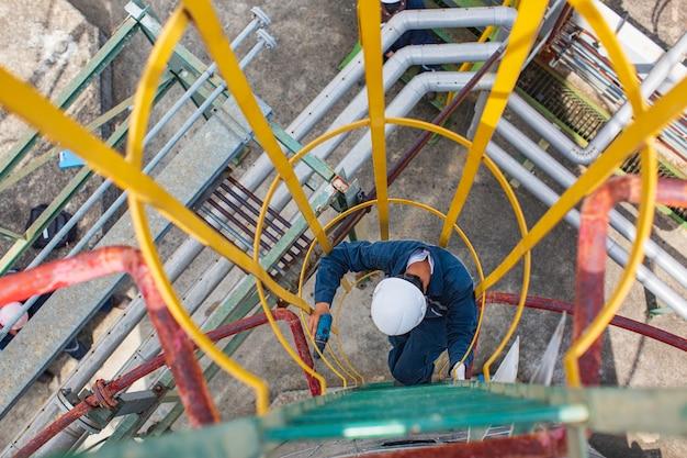 Vista superior masculina suba a escada da escada, armazenamento, inspeção visual, óleo do tanque