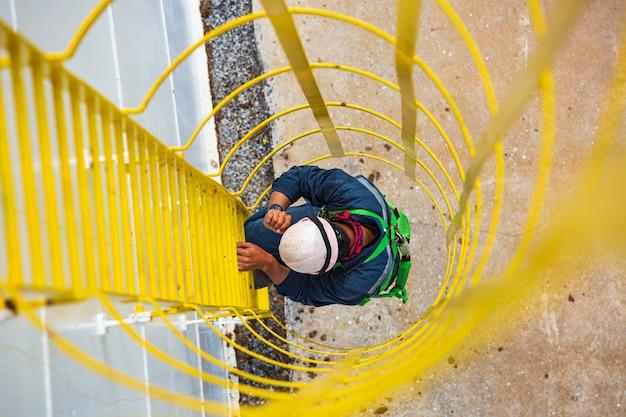 Vista superior masculina subir a escada de armazenamento de óleo do tanque de inspeção visual