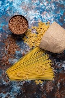 Vista superior massa amarela crua formada e pouco com trigo sarraceno em todo o fundo colorido.