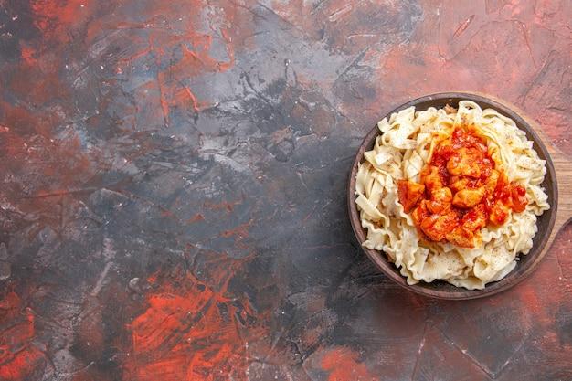 Vista superior massa cozida com fatias de frango e molho em prato escuro de massa de massa