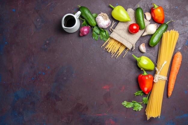 Vista superior massa crua de ingredientes diferentes e vegetais frescos em superfície escura produto refeição fresca salada dieta saudável