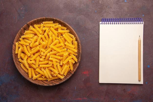 Vista superior massa italiana crua pouco formada dentro do prato sobre fundo roxo-escuro massa alimentícia Foto gratuita