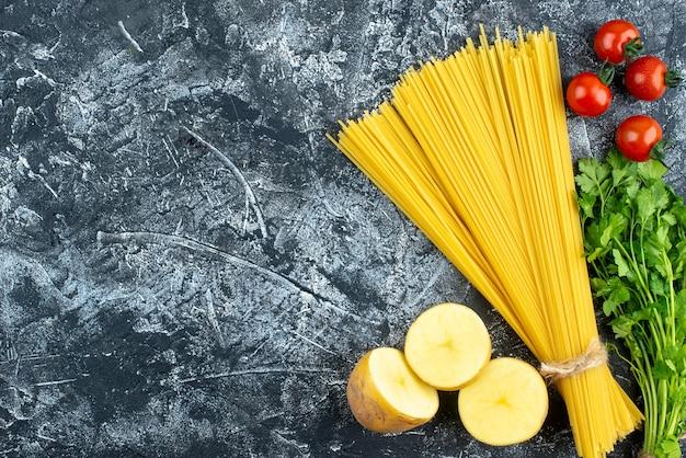 Vista superior massa longa crua com verduras e tomates em cor de fundo cinza.