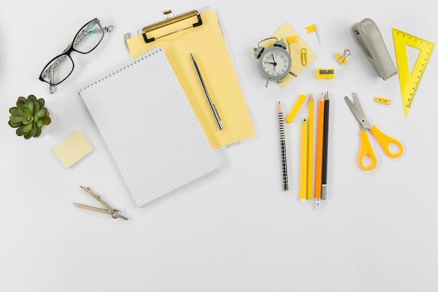 Vista superior material de escritório com o bloco de notas em cima da mesa