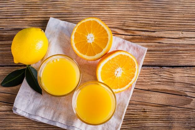 Vista superior meio corte laranjas e copos com suco