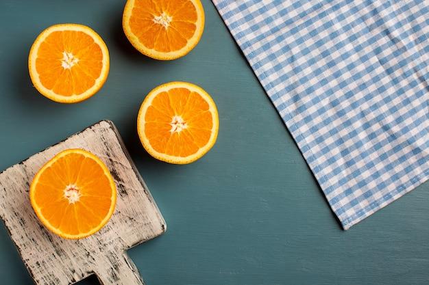 Vista superior meio corte laranjas e toalha